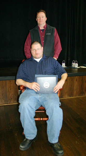 Penn State Hazleton Maintenance Worker David Phillips received a Penn State rocking chair to commemorate his 25 years of service to the University. Standing is Maintenance Supervisor Michael Chura.